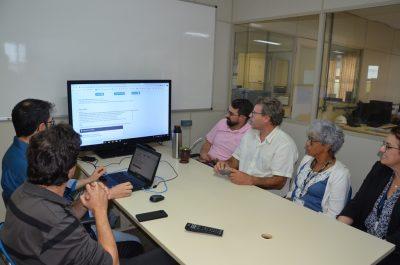 Junta eleitoral reunida em torno de uma mesa, analisando o resultado da votação, que ocorreu de forma eletrônica.