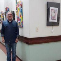 Artista posa em frente ao corredor com suas telas