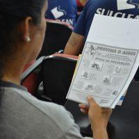 Moça lê folheto com orientações de combate ao mosquito