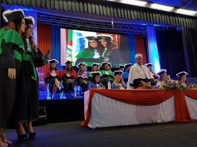 Estudante recebe o canudo na primeira formatura institucional da UFPel, com mesa de autoridades ao fundo
