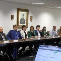 Na mesa de reuniões, o vice-reitor e as duas gestoras do Biotério da UFPel