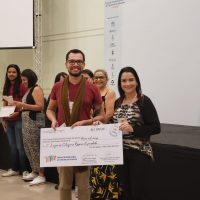 Aluno premiado e orientadora recebem prêmio no evento.