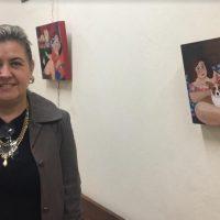 Artista posa em frente às obras no Corredor Arte