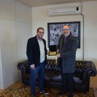 Reitor da Católica entrega placa ao dirigente máximo da UFPel.