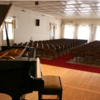 Salão Milton de Lemos, com piano em primeiro plano e cadeiras ao fundo