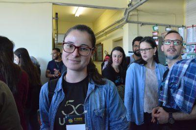 Mariana olha para a câmera, pessoas passam ao fundo
