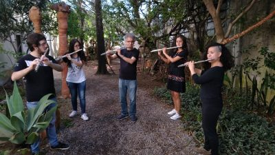 Alunos e professor tocando flautas no jardim