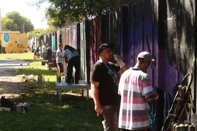 artistas trabalham no muro do Campus