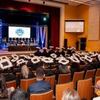 Cerimônia de formatura, com formandos na plateia e mesa de autoridades ao fundo