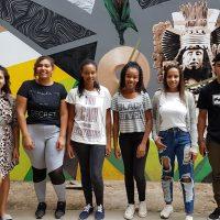 Grupo de novos alunos quilombolas e indígenas posa em frente a mural no Campus Anglo